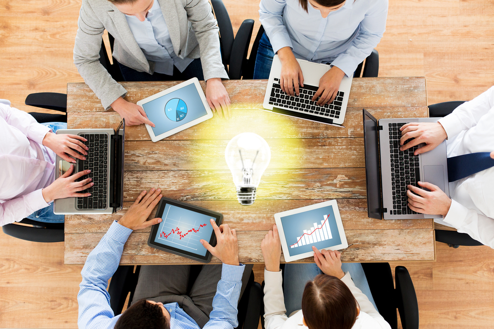 business, people and technology concept - close up of creative team with laptop and tablet pc sitting at table in office over lighting bulb